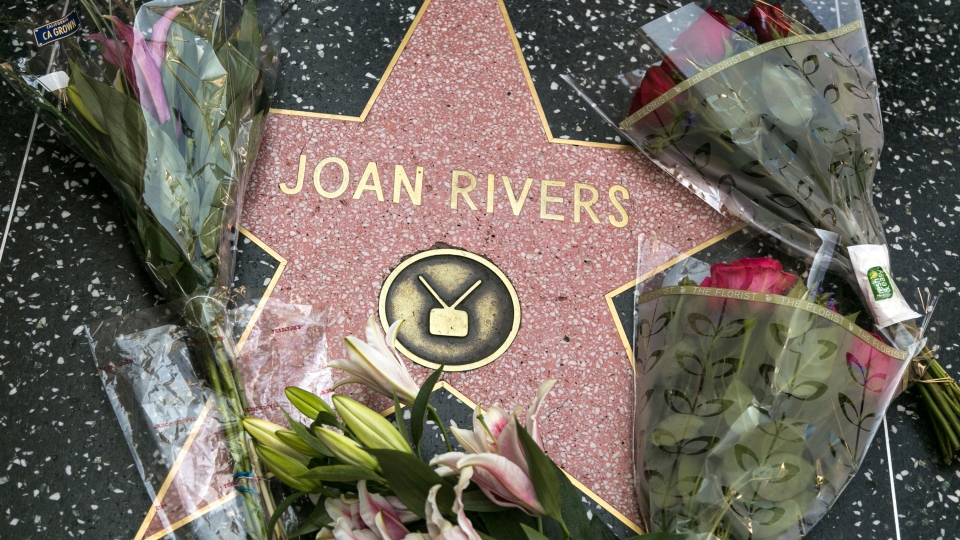 Flowers surround Joan Rivers' star on the Hollywood Walk of Fame in Los Angeles. Rivers, the raucous, acid-tongued comedian who crashed the male-dominated realm of late-night talk shows and turned Hollywood red carpets into danger zones for badly dressed celebrities, died Thursday. She was 81. (AP / Damian Dovarganes)