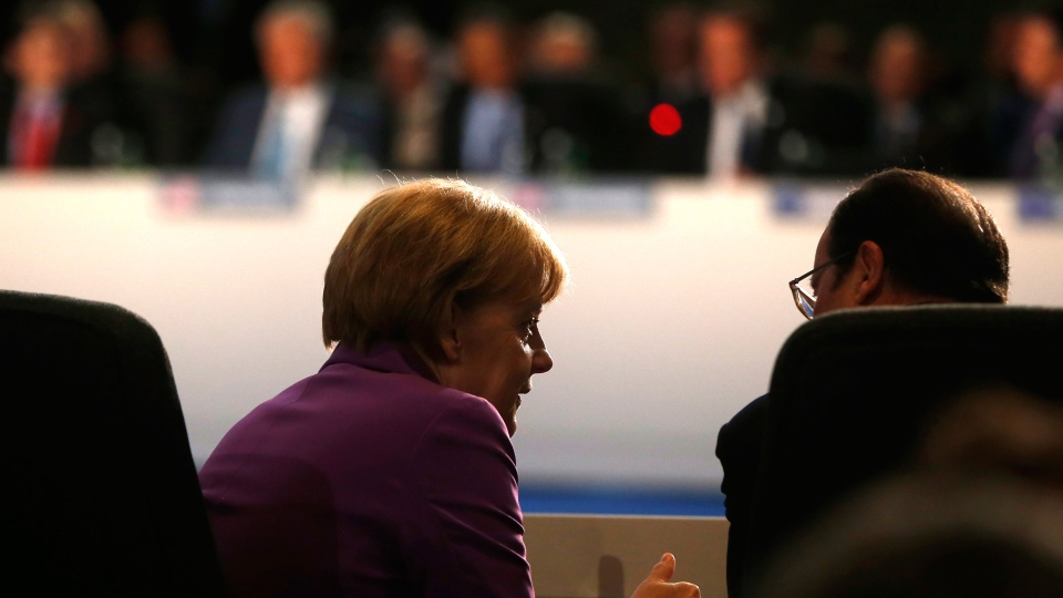 German Chancellor Angela Merkel, left, speaks with French President Francois Hollande, right, at a leaders meeting on the future of NATO at Celtic Manor, Newport, Wales, Friday, Sept. 5, 2014. (AP / Charles Dharapak)