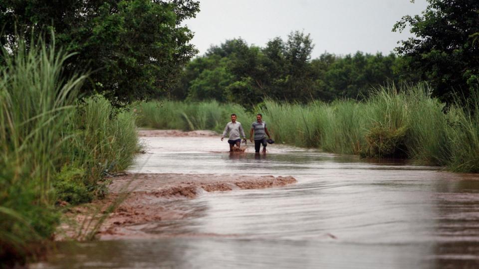 Residents wade in the River Chenab at Garkhal village, 35 kilometres from Jammu, India, Friday, Sep. 5, 2014. (AP / Channi Anand)
