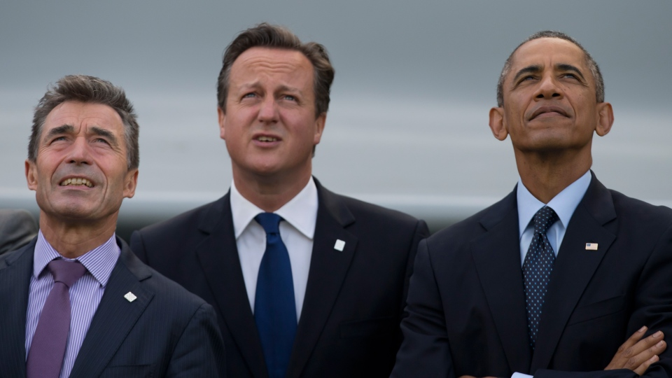 U.S. President Barack Obama, right, stands alongside British Prime Minister David Cameron, centre, and NATO Secretary General Anders Fogh Rasmussen during a flypast at the NATO summit at the Celtic Manor Resort in Newport, Wales on Friday, Sept. 5, 2014. (AP / Jon Super)