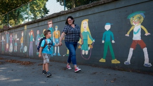 Gwen Floyd shows her youngest son Quinlan Floyd, 4, around the school grounds outside L'Ecole Bilingue Elementary School in Vancouver, B.C., on Tuesday August 20, 2013. (Darryl Dyck / THE CANADIAN PRESS)