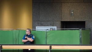 A Montreal Courthouse special constable stands next to screens to shield the identities of potential jurors as jury selection begins in the Luka Magnotta murder trial in Montreal, Monday, Sept. 8, 2014. (Graham Hughes / THE CANADIAN PRESS)