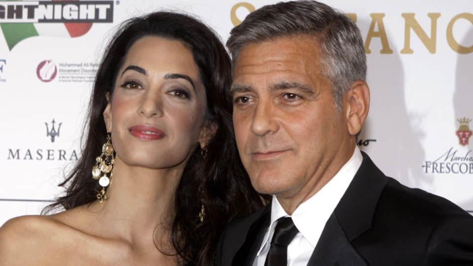 George Clooney, seen with wife and world-renowned human rights lawyer Amal Clooney, pose in Florence, Italy, on Sept. 7, 2014. The American actor says the Canadian government should do everything they can to free jailed Canadian journalist Mohamed Fahmy from an Egyptian prison. (Francesco Bellini/AP Photo)