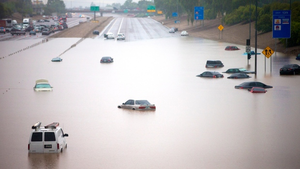 Heavy storms pounded the Phoenix, Az. area early Monday, flooding major freeways, prompting several water rescues and setting an all-time single-day record for rainfall in the desert city Monday, Sept. 8, 2014. <br><br> Cars are stuck in flood waters on I-10 east at 43rd Ave. (AP / The Arizona Republic, Michael Chow)