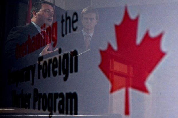 Employment Minister Jason Kenney, left, and Immigration Minister Chris Alexander are seen in a reflection at a news conference in Ottawa on Friday, June 20, 2014 on reforms to the Temporary Foreign Worker Program. THE CANADIAN PRESS/Sean Kilpatrick