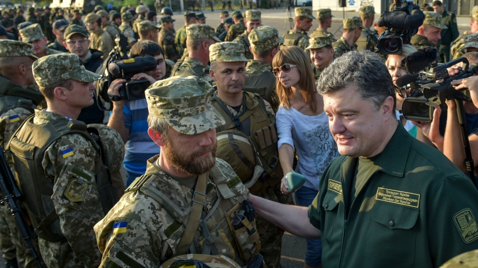 Ukrainian President Petro Poroshenko, right, inspects military personnel during his visit to the southern coastal town of Mariupol, Ukraine, Monday, Sept. 8, 2014. (AP / Mykola Lazarenko)