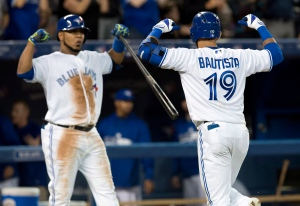 Toronto Blue Jays Jose Bautista celebrates his 3-run homer with teammate Edwin Encarnacion during fifth inning action against the Chicago Cubs in Toronto on Monday, Sept. 8, 2014. (The Canadian Press/Frank Gunn)