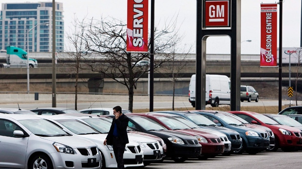 file a man walks past cars at a general motors dealership in toronto. Cars Review. Best American Auto & Cars Review