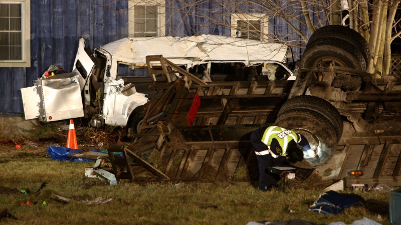 Ontario Provincial Police and emergency crews investigate a multiple fatal motor vehicle accident near Hampstead, Ontario, Monday, Feb. 6, 2012. Police say 11 people died in the crash. (Dave Chidley / THE CANADIAN PRESS)