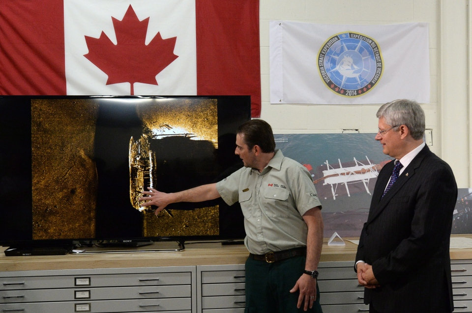 Prime Minister Stephen Harper listens to details from Parks Canada's Ryan Harris about the find from the Victoria Strait Expedition in Ottawa on Tuesday September 9, 2014. (Sean Kilpatrick / THE CANADIAN PRESS)