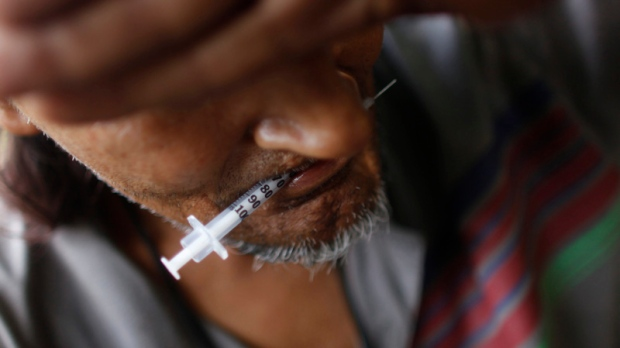 A heroin addict holds a used syringe in his teeth after shooting up in an abandoned lot in San Juan, Friday, July 31, 2009. Some of the South American heroin trafficked through Puerto Rico en route to the United States is sold locally, which has led to an island-wide epidemic, according to health and law enforcement officials. (AP Photo/Brennan Linsley)