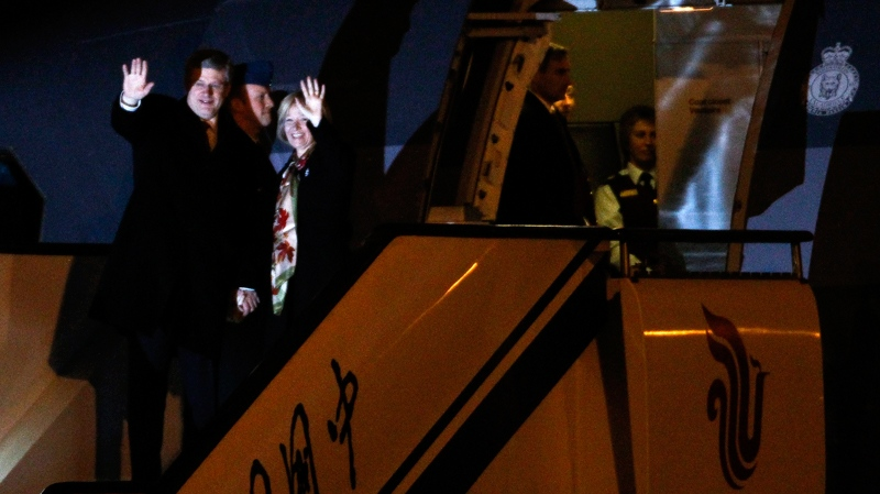 Prime Minister Stephen Harper and his wife Laureen Harper wave as they arrive at Capital International Airport in Beijing Tuesday, Feb. 7, 2012. (AP / Alexander F. Yuan)