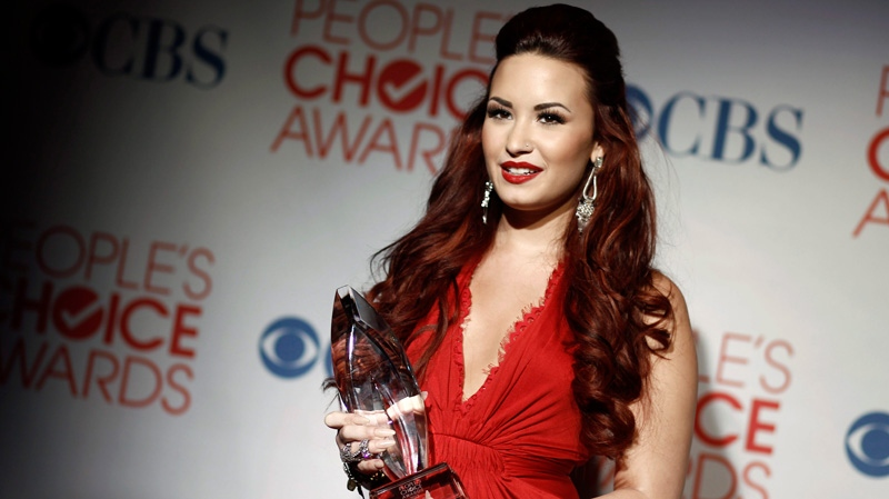 Demi Lovato poses backstage with the award for favorite pop artist at the People's Choice Awards in Los Angeles, Wednesday, Jan. 11, 2012. (AP / Matt Sayles)