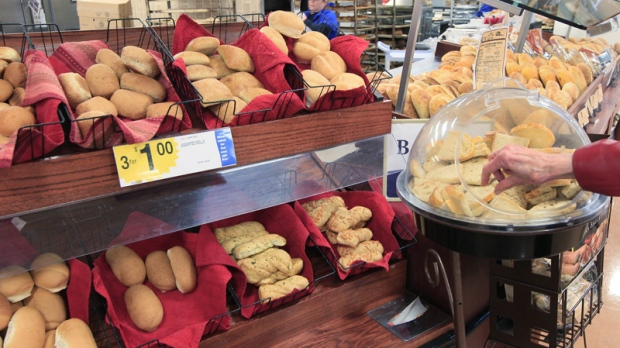A customer samples some fresh baked bread at a grocery store in Cincinnati on Tuesday, Feb. 7, 2012. (AP Photo/Al Behrman)