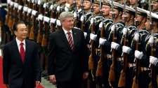 Chinese Premier Wen Jiabao, left, and Canadian Prime Minister Stephen Harper walk together to review an honor guard during a welcoming ceremony at the Great Hall of the People in Beijing Wednesday, Feb. 8, 2012. (AP / Alexander F. Yuan)