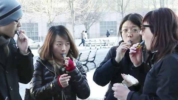 In this Monday, Jan. 23, 2012 still photo taken from video, students try free samples of AeroShot, an inhalable caffeine packed in a lipstick-sized canister, on the campus of Northeastern University in Boston.