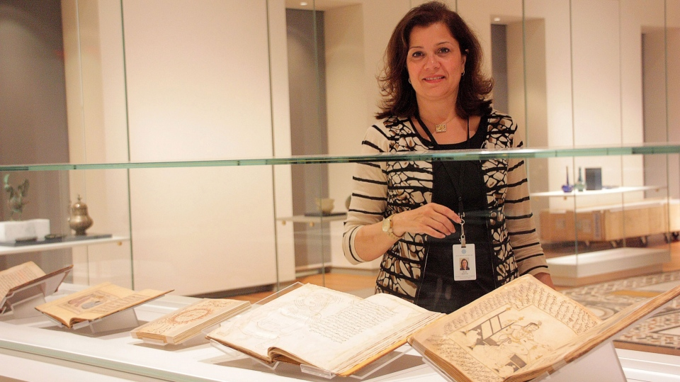 Ruba Kana'an, head of education and scholarly programs, looks at some of the artifacts on display at the new Aga Khan museum in Toronto on Tuesday, Sept. 9, 2014. (Colin Perkel / THE CANADIAN PRESS)