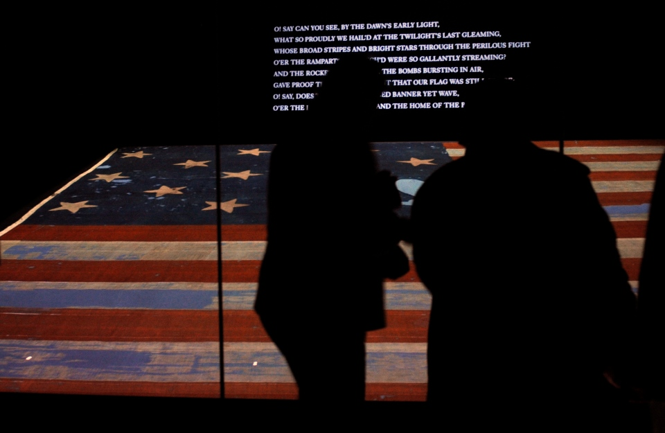 Visitors look at the original Star Spangled Banner, the flag that inspired the national anthem, inside a protective chamber at the National Museum of American History in Washington, on Nov. 21, 2008. (AP / Jacquelyn Martin)