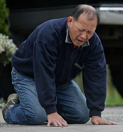 A man breaks down after three people were overcome by an unknown substance and died at a mushroom farm in Langley, B.C., on Friday September 5, 2008. (THE CANADIAN PRESS/Darryl Dyck)