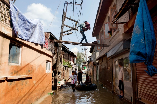 Residents sift through damaged homes as floodwaters in Indian-held Kashmir have receded allowing passage back into ravaged neighbourhoods. A Kashmiri-man carries items salvaged from his damaged house and he walks on a ladder to reach his neighbor's house in Srinagar, Indian-held Kashmir, Saturday, Sept. 13, 2014.   About 200 people have died in Indian-controlled Kashmir, where floodwaters have receded, enabling people to return to their homes. Medical teams in Srinagar, the main city in Indian-held Kashmir, were stepping up efforts to prevent the spread of waterborne diseases, officials said Saturday. (AP / Dar Yasin)