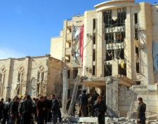In this photo released by the Syrian official news agency SANA, Syrian security forces gather in front a damaged building at a security compound which was attacked by an explosion, in the northern city of Aleppo, Syria, on Friday, Feb. 10, 2012. (SANA)