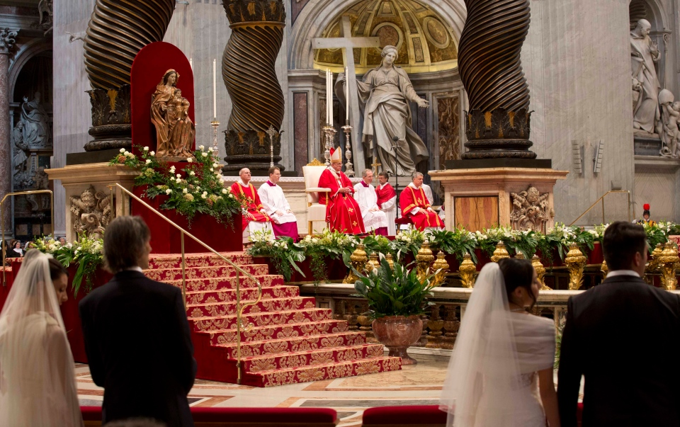 Newly married couples attend a wedding ceremony led by Pope Francis in St. Peter's Basilica at the Vatican, Sunday, Sept. 14, 2014. Pope Francis married 20 couples, including some who already live together and those with children, technically a sin in the eyes of the church. (AP/Alessandra Tarantino)