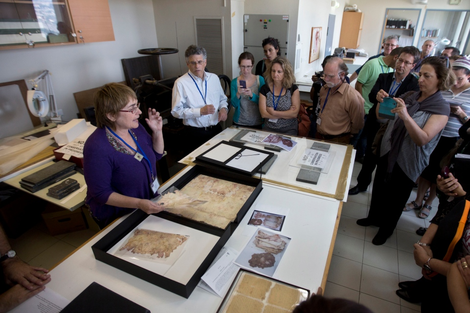 A worker shows restored documents at the Yad Vashem Holocaust memorial paper conservation laboratory to visiting international experts and others participating in a workshop devoted to the physical and digital preservation of documents, in Jerusalem on Monday, Sept. 8, 2014. (AP / Sebastian Scheiner)