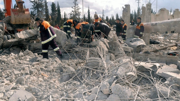 In this photo released by the Syrian official news agency SANA, Syrian rescue workers remove wreckage from a destroyed building at a security compound which was attacked by an explosion, in the northern city of Aleppo, Syria, on Friday, Feb. 10, 2012. (SANA)