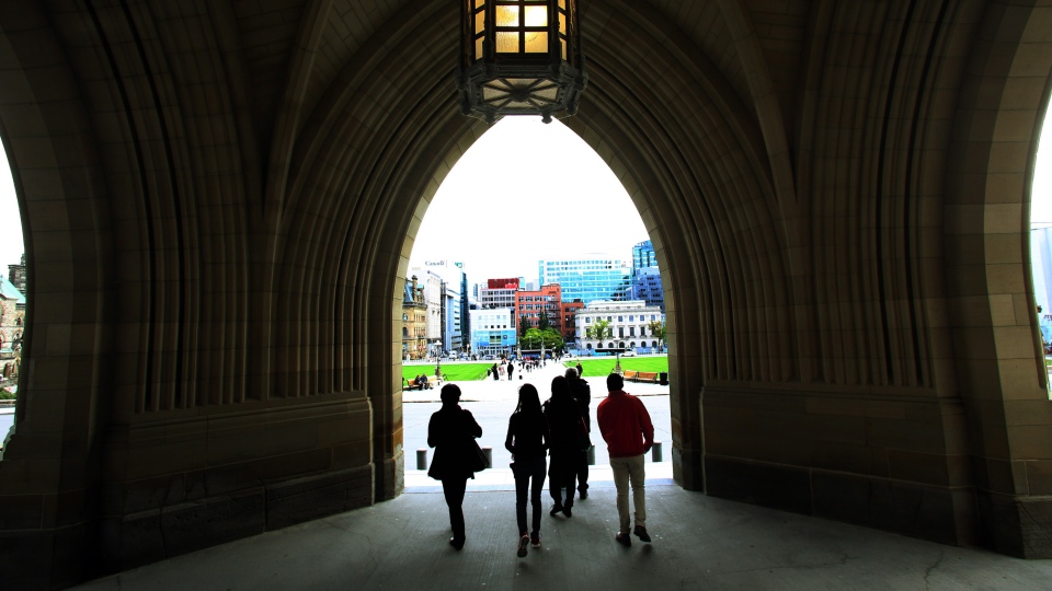 A group tourists leave the Parliament Buildings below the Peace Tower of the Parliament Hill in Ottawa. Parliamentiarns will return to work today after the summer break. (Fred Chartrand / THE CANADIAN PRESS)