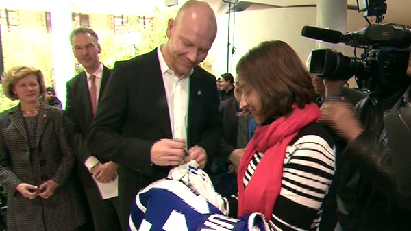 Former Toronto Maple Leafs captain Mats Sundin signs a jersey for a fan at the University of Toronto, Friday, Feb. 10, 2012