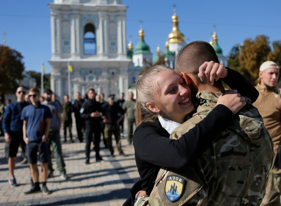 A fighter from the Azov volunteer battalion hugs his girlfriend after returning from rotation at the front line in Kyiv, Ukraine, Sept. 15, 2014 file photo. (AP / Sergei Chuzavkov)