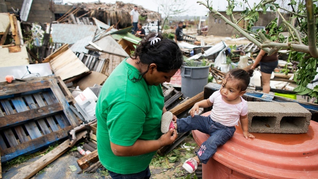 Maria Ramirez, left, puts the shoes on her one-year-old niece Maritza next to the remains of their home that was destroyed by Hurricane Odile in Los Cabos, Mexico, Monday, Sept. 15, 2014. <br> <br> 
