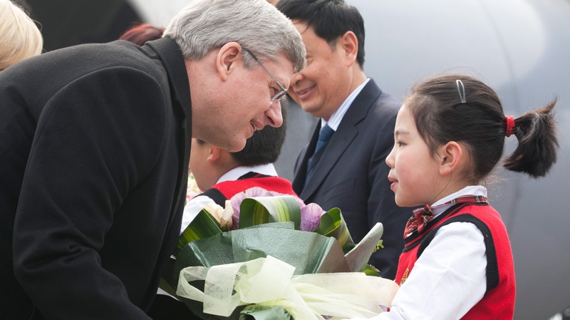 Canadian Prime Minister Stephen Harper is presented with flowers as he arrives in Chongqing, Saturday, Feb.11, 2012.