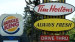 A Burger King sign and a Tim Hortons sign are displayed on St. Laurent Boulevard in Ottawa on August 25, 2014. (THE CANADIAN PRESS / Sean Kilpatrick)