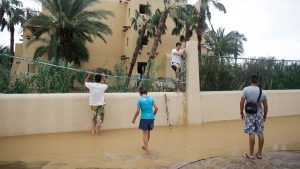 Tourist Cesar Calzada, centre, of Mexico City, climbs over a fence of the Riu resort to get out of the hotel and go search for food after Hurricane Odile severely damaged the hotel in Los Cabos, Mexico, Monday, Sept. 15, 2014. (AP / Victor R. Caivano)