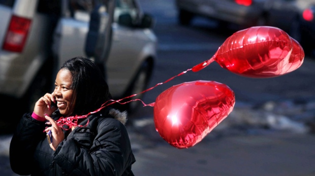 MATC nursing student Tonya Cox, outside the downtown Madison campus, holds heart-shaped balloons given to her by a friend and talks on her cell phone on Valentine's Day, Monday, Feb. 14, 2011, in Madison, Wis.