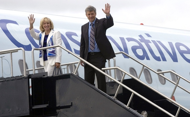 Conservative Party Leader Stephen Harper and his wife Laureen wave before boarding his campaign plane enroute to Quebec City for his first campaign stop, in Ottawa, Sunday, Sept. 7, 2008. (Tom Hanson / THE CANADIAN PRESS)