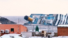 Snow covers the rooftops of the houses overlooking the harbour of the Tuscan island of Giglio, Italy, Saturday, Feb. 11, 2012, as the grounded Costa Concordia cruise liner still lays stricken in background.
