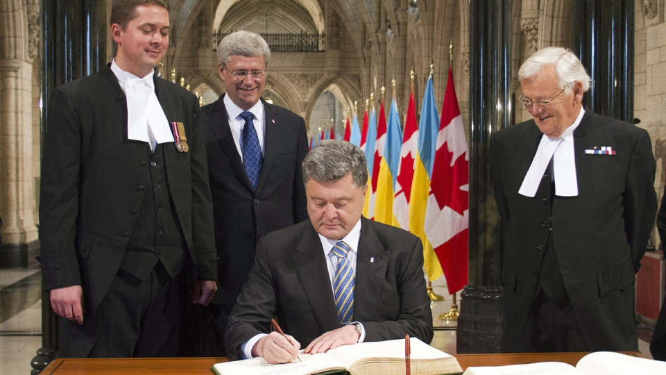 House Speaker Andrew Scheer and Prime Minister Stephen Harper and Senate Speaker Noel A. Kinsella, left to right, look on as Ukrainian President Petro Poroshenko, foreground, signs the book of Honour on Parliament Hill, in Ottawa, Wednesday, Sept.17, 2014. (Fred Chartrand / THE CANADIAN PRESS)