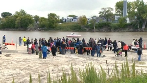 People gather along the banks of the Red River during a search, in Winnipeg, Sunday, Sept. 14, 2014.