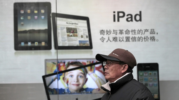 In this file photo taken on Jan. 26, 2011, a man stands near Apple's iPad advertisement in Shanghai, China. (AP Photo/Eugene Hoshiko, File)
