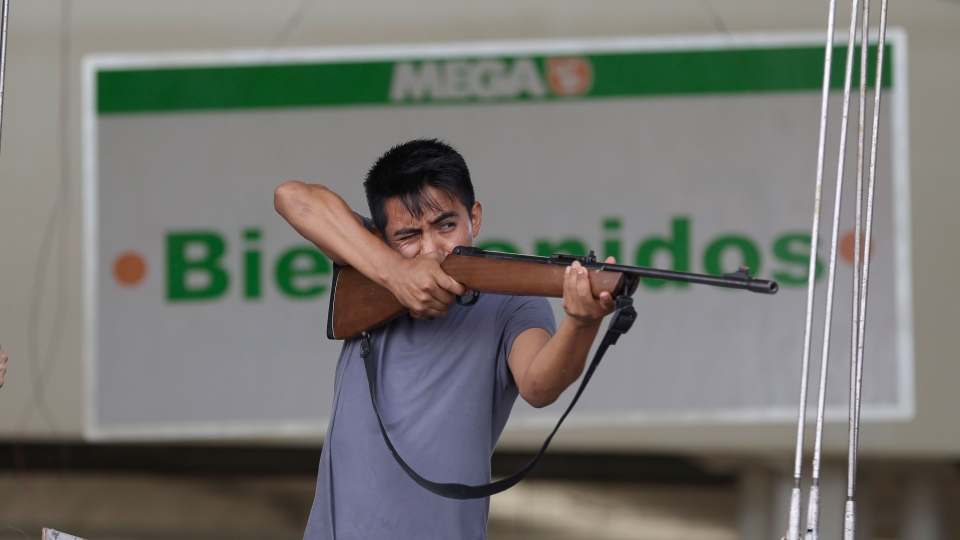 An employee from Mega Supermarket fires an air rifle at people trying to loot the store in Los Cabos, Mexico, Tuesday, Sept. 16, 2014. (AP / Victor R. Caivano)