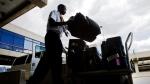 Baggage handler Mikaaill Heard loads luggage on May 21, 2008. (AP / Matt Rourke)