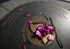 Flowers placed on a Grammy sidewalk plaque honouring Whitney Houston's wins for Record of the Year and Album of the Year in 36th Grammy Awards, have been scattered and replaced several times outside the Grammy Museum in Los Angeles. (AP / Reed Saxon)