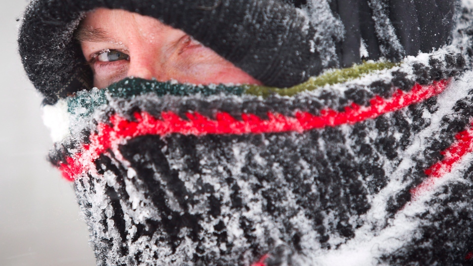 David Reid peers out from his wrappings as he uses a snow blower to clear his driveway during a blizzard last year near Cremona, Alberta. (Jeff McIntosh / THE CANADIAN PRESS)