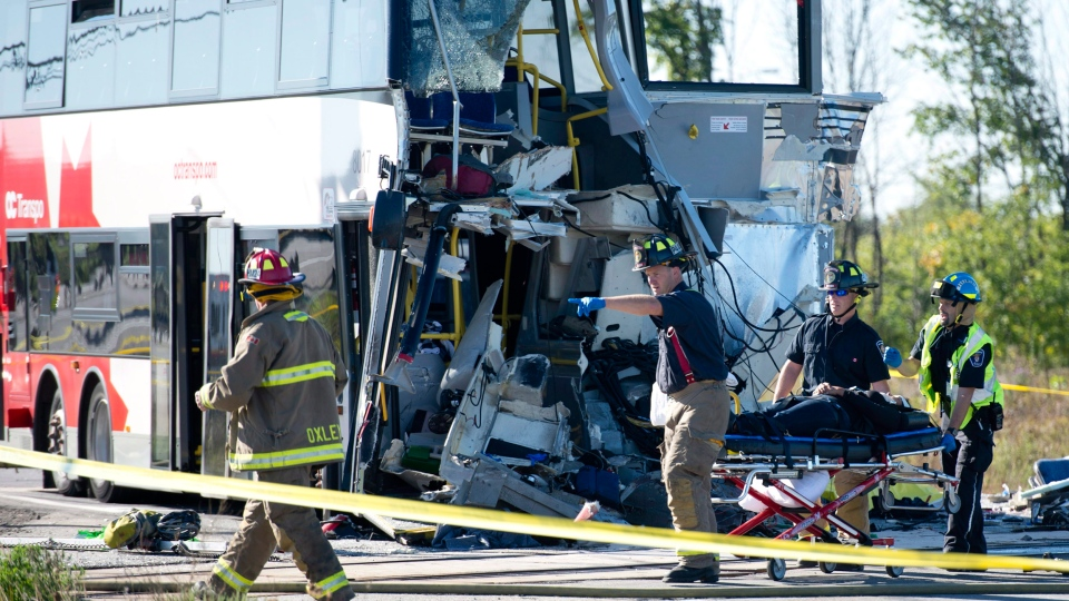 Firefighters and paramedics move a passenger to a waiting ambulance after a Via Rail train and transit bus collided in Ottawa, Wednesday, Sept. 18, 2013. (Adrian Wyld / THE CANADIAN PRESS)