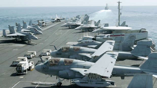A picture taken from the bridge of the Nimitz-class aircraft carrier USS Abraham Lincoln shows U.S. aircraft parked on the flight deck as a U.S. destroyer, background, patrols the Arabian sea in the Strait of Hurmuz, Tuesday, Feb. 14, 2012. (AP / Hassan Ammar)