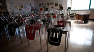A vacant teachers desk is pictured at the front of a empty classroom is pictured at McGee Secondary school in Vancouver on Sept. 5, 2014. B.C.'s public school teachers have ratified a hard-bargained six-year contract, ending a bitter months-long strike and allowing the start of the school year for half a million students. THE CANADIAN PRESS/Jonathan Hayward