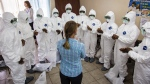 A WHO worker, centre, trains nurses to use Ebola protective gear in Freetown, Sierra Leone, on Sept. 18, 2014. (AP / Michael Duff)