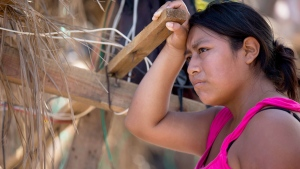 A woman pauses as she leans against a wooden slat that is part of her home, destroyed by Hurricane Odile in San Jose de los Cabos, Mexico, Thursday, Sept. 18, 2014. (AP / Dario Lopez-Mills)